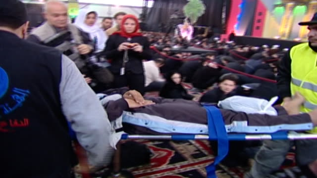 lebanese red crescent medical staff taking a person out of the majlis, who has fainted, during the ashura commemoration organised by hezbollah in... - シャイフ点の映像素材/bロール