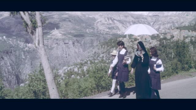 1968 lebanon - nun walking with 3 students - lebanon country stock videos & royalty-free footage
