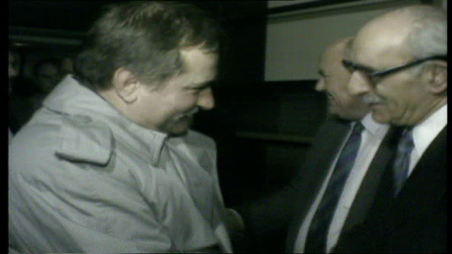 lech walesa along walkway heathrow towards and greeted by norman willis airport and ron todd : all three holding hands for pictures: ext 04:03... - 労働組合会議点の映像素材/bロール