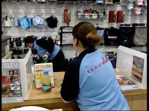 Leeds board meet to discuss relegation ITN Leeds INT Shop assistant in sports store putting Leeds shirts on rack