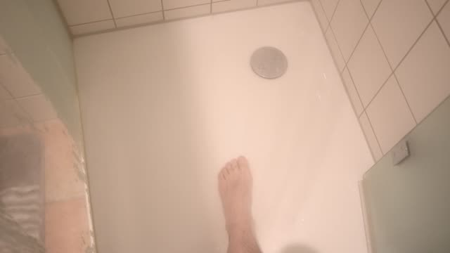 left foot of man on the shower tray. hot drops of water fall on the foot - 排水口点の映像素材/bロール