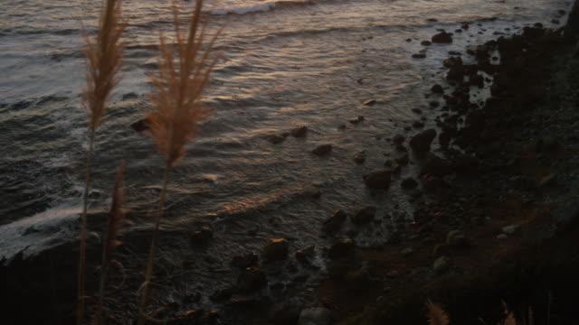 vídeos de stock e filmes b-roll de left right coastline sunset tilt up - gema semipreciosa