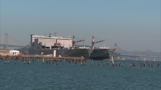 vídeos de stock e filmes b-roll de san francisco bay, moored, docked military, navy roll-on/roll-off ships , san francisco-oakland bay bridge bg. maritime, marine. - desodorante