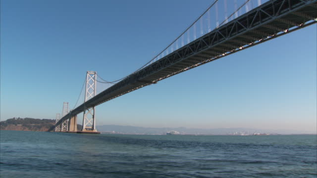 san francisco bay, passing underneath san francisco-oakland bay bridge, fog & hills bg, suspension, cantilever, truss, infrastructure. - cantilever bridge stock videos & royalty-free footage