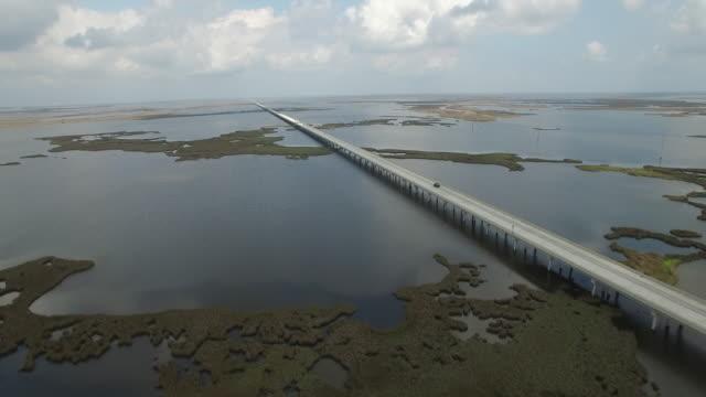 left to right over causeway long bridge - Drone Aerial 4K Lake Pontchartrain CausewayGrand Isle Louisiana coast Mississippi river bridge and barge everglades, gulf delta, with wildlife 4K Transportation