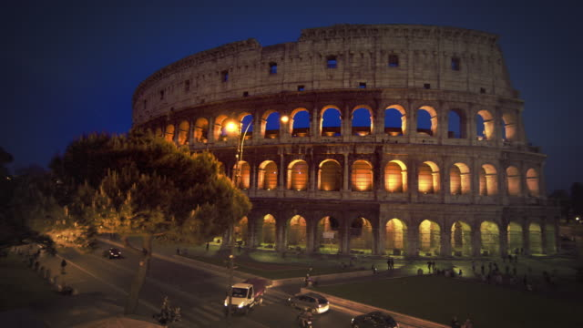 left-to-right pan of intersection and colosseum at night - geschichtlich stock-videos und b-roll-filmmaterial