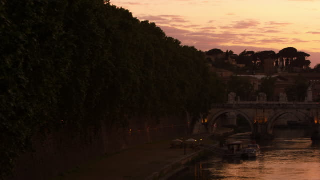 left-to-right pan of ponte sant'angelo and dome of st. peter's basilica at sunset - サンタンジェロ橋点の映像素材/bロール