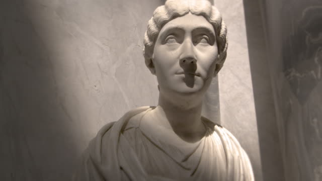 Left-to-right tracking shot of female bust in the New Wing