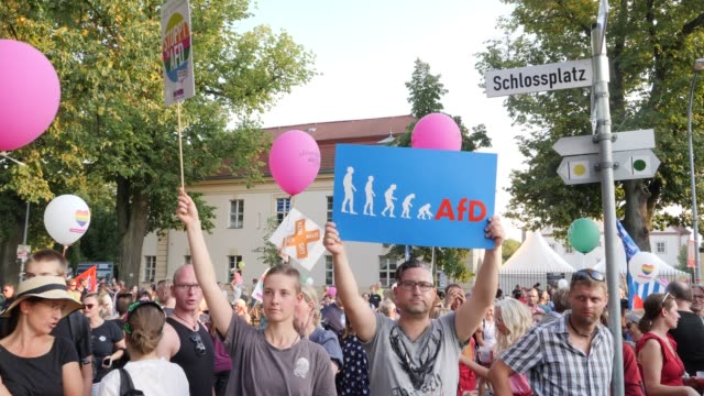 leftwing orientated protesters demonstrate with selfmade posters against the alternative for germany which simultaneously organized in the opposite... - respekt stock-videos und b-roll-filmmaterial