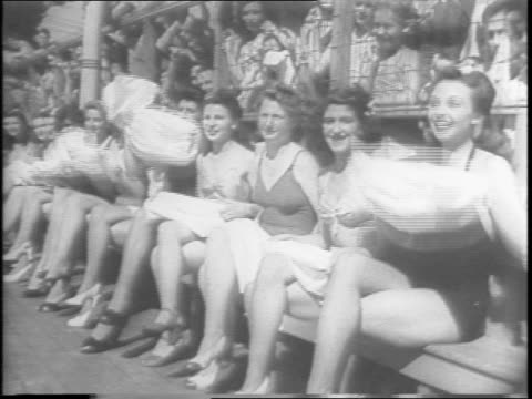 Leg Day at Palisades Park brings shapelylimbed contestants before allservice jury for 1943 Leg's Queen title / line of contestants sitting on bench...