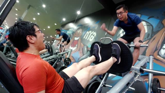 vídeos de stock, filmes e b-roll de o exercício do dia do pé de homens asiáticos exercita o pé do treinamento com amigo na ginástica. - testamento