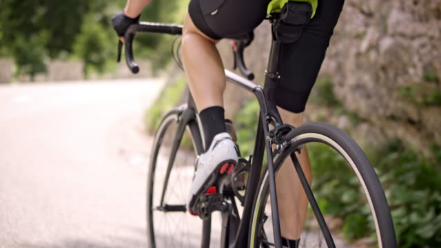 slo mo leg of a road cyclist pushing the pedals up an asphalt road in sunshine - competenza video stock e b–roll