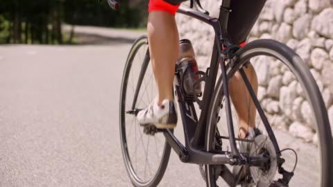 stockvideo's en b-roll-footage met slo mo poot van vrouwelijke wielrenner duwen van de pedalen op haar fiets op een asfaltweg in de zon - cycling