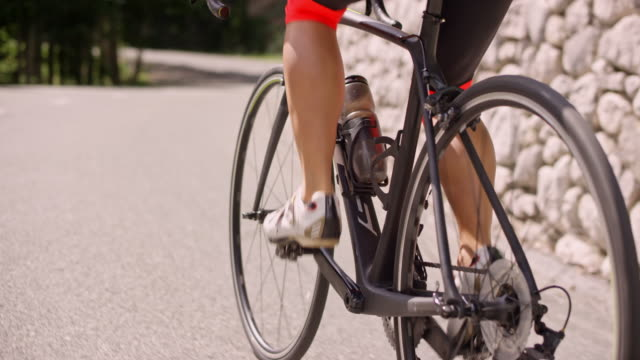 vídeos de stock e filmes b-roll de slo mo leg of female road cyclist pushing the pedals on her bike up an asphalt road in sunshine - ciclismo