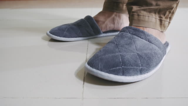leg of man wear fur home slippers shoes color gray and walking inside home. - slipper stock videos & royalty-free footage