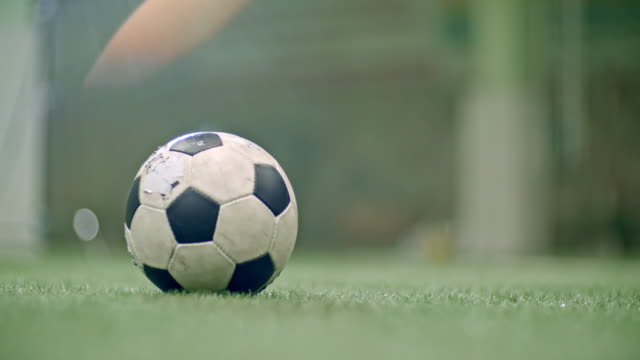 Leg of soccer player kicking ball