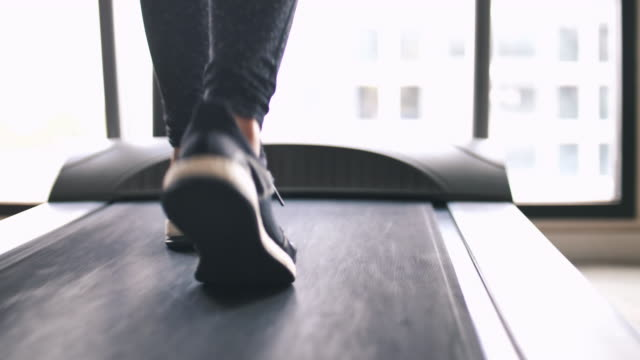 leg of woman running on treadmill - scarpe da ginnastica video stock e b–roll