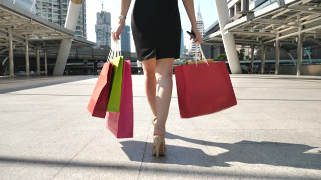 leg of young woman walks with shopping bags - mid section stock videos and b-roll footage