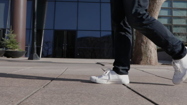 leg profile of an adult man walking in sneakers on the sidewalk in front of the building in seoul - profile stock-videos und b-roll-filmmaterial