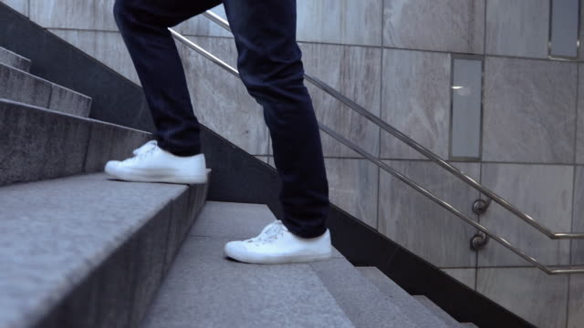 leg profile of an adult man walking up the stairs to the exit of the subway station in seoul - steps and staircases stock videos & royalty-free footage