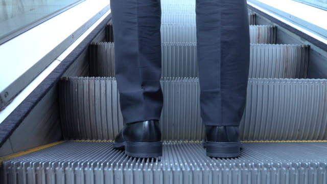 leg rear view of an adult man that goes up the escalator of underpass in seoul - standing点の映像素材/bロール
