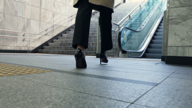 leg rear view of an adult woman that goes up the escalator of underpass in seoul - escalator stock videos & royalty-free footage