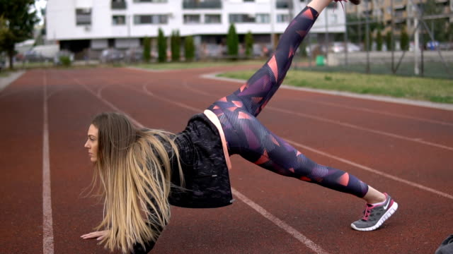 Leg stretching on a running track by female fitness instructor