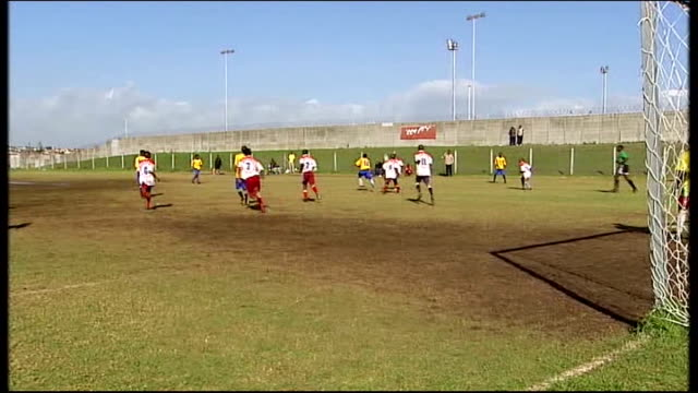 legacy local team playing football at khayelitsha stadium on uneven boggy ground and handful of supporters watching from sidelines woman selling... - uneven stock videos & royalty-free footage