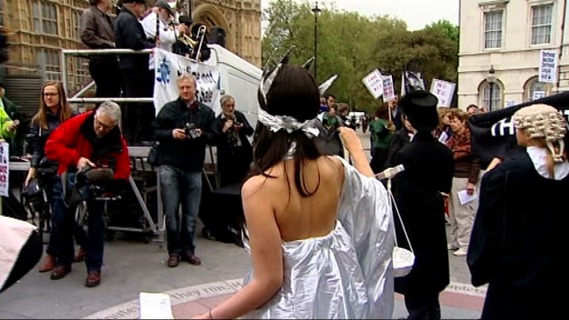 Legal Aid protest in Westminster Shots of women's group protesters with posters and banners / 'Scales of Justice' protester having blindfold put on /...