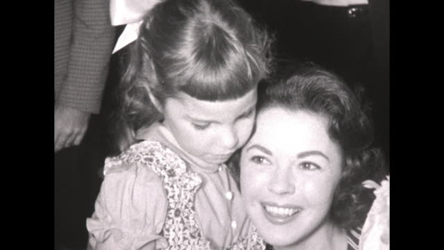 vídeos de stock e filmes b-roll de legendary child film star / celebrity shirley temple in her adult age shows off her vast collection of doll toys to young children the dolls are... - shirley temple