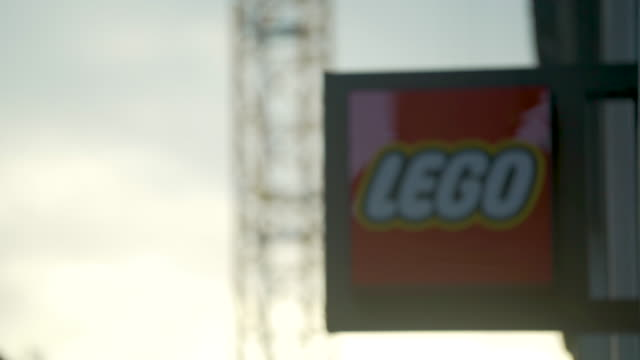 lego shop sign against a bright sky with varied exposures; crane moving in background - multiple exposure stock videos & royalty-free footage