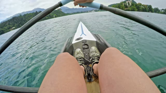 pov legs and arm of female athlete sculling on a lake - scull stock videos & royalty-free footage