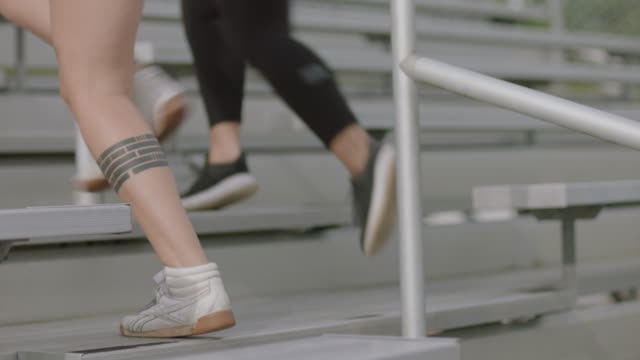 vídeos de stock e filmes b-roll de slo mo. cu of legs and feet of a group of active women running up the staircase of a set of bleachers for exercise - degraus