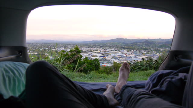 vídeos y material grabado en eventos de stock de pov of legs and feet of man lying down camping in the back of his suv car vehicle above a city. - slow motion - identidad