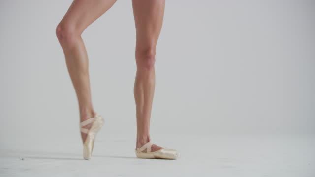vídeos y material grabado en eventos de stock de legs and feet of woman ballet dancer dancing, practicing, and warming up in studio - de puntas