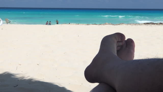 Legs and feet relaxing with the sea in the horizon