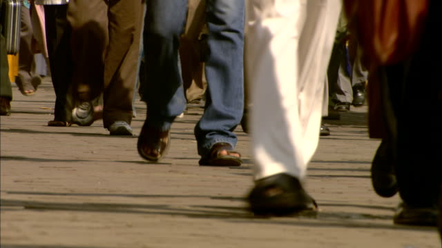 legs and feet walk down a crowded street in india. - population explosion stock videos & royalty-free footage