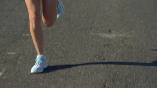 vídeos y material grabado en eventos de stock de slo mo ms pan tu legs and torso of woman running on road / cape town, south africa - triatlón