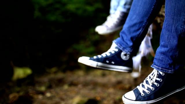 vídeos y material grabado en eventos de stock de piernas colgando hacia abajo - zapatillas de deporte