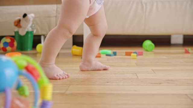 slo mo legs of a barefoot baby walking in the living room - primi passi video stock e b–roll