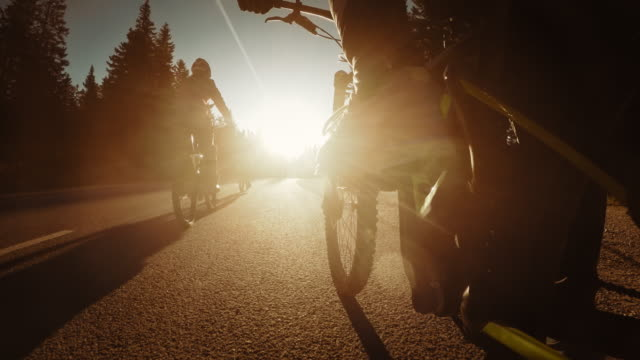 pov legs of a biker riding into the sunset - asphalt stock videos & royalty-free footage
