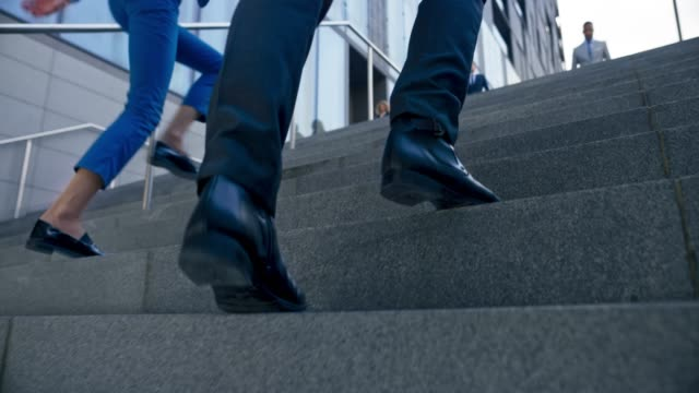 slo mo ts legs of a business man wearing black shoes and business suit walking up the stairs outside the  business building - edificio adibito a uffici video stock e b–roll