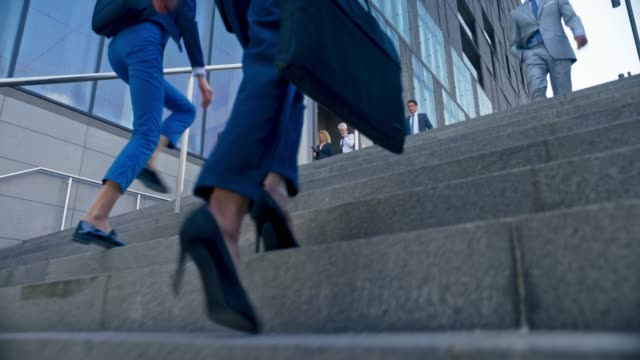 vídeos de stock e filmes b-roll de ts legs of a business woman in high heels walking up the stairs in front of a modern business building amongst other people - degraus