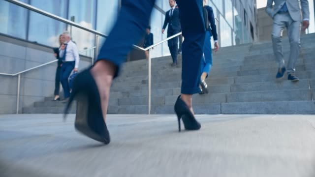 slo mo ts legs of a business woman wearing high heels and business suit walking up the stairs outside the  business building - human leg stock videos & royalty-free footage