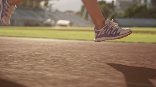 日当たりの良いスタジアムで実行している白人女性アスリートの slo mo ts 足 - 陸地点の映像素材/bロール