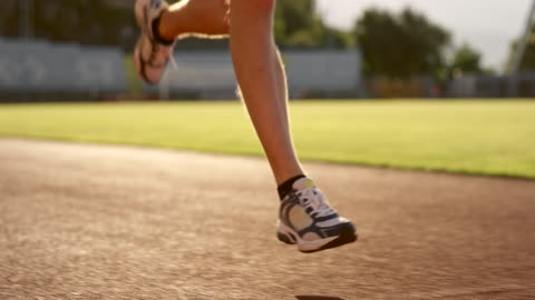 slo mo legs of a caucasian man running in the stadium at sunset - track and field stock videos & royalty-free footage