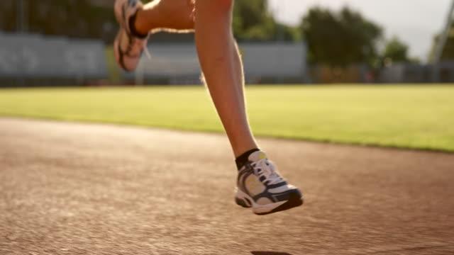 vidéos et rushes de slo mo jambes d'un homme de race blanche en cours d'exécution dans le stade au coucher du soleil - piste de compétition