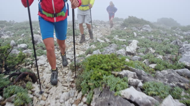 Legs of a female hiker walking up the mountain with her friends in heavy fog