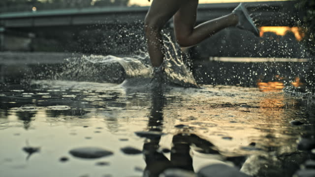 slo mo legs of a female runner running across puddles - running stock videos & royalty-free footage