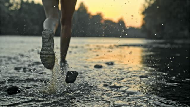 vídeos de stock, filmes e b-roll de slo mo as pernas de um corredor feminino correndo pelo rio - aventura